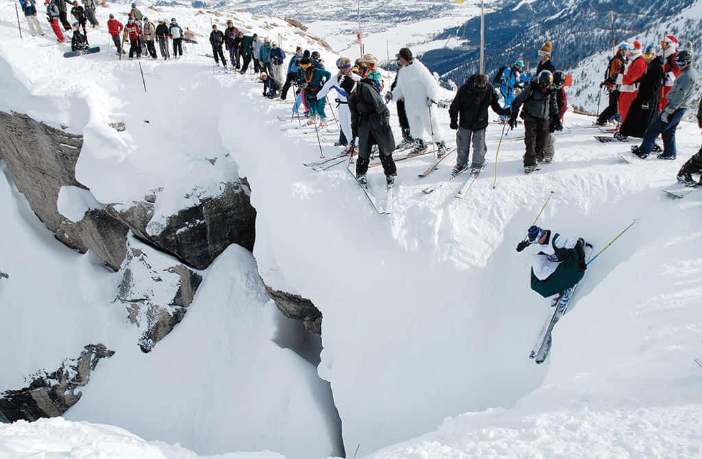 Costumed spectators line the cliff band above Corbet's Couloir as a skier takes the plunge on the last day of the season at Jackson Hole Mountain Resort. Photograph by Bradly J. Boner
