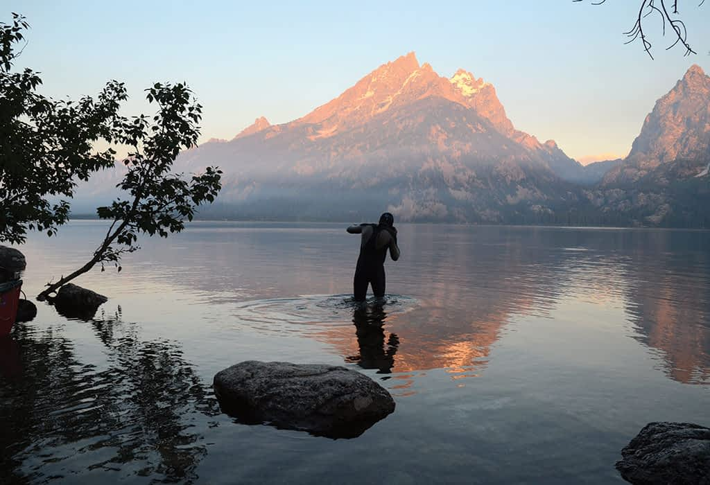 After riding 21 miles from Jackson to Grand Teton National Park, David Gonzales dons a wetsuit and goggles for a sunrise swim across Jenny Lake. After the swim Gonzales summited the Grand Teton, and then did the entire route in reverse.