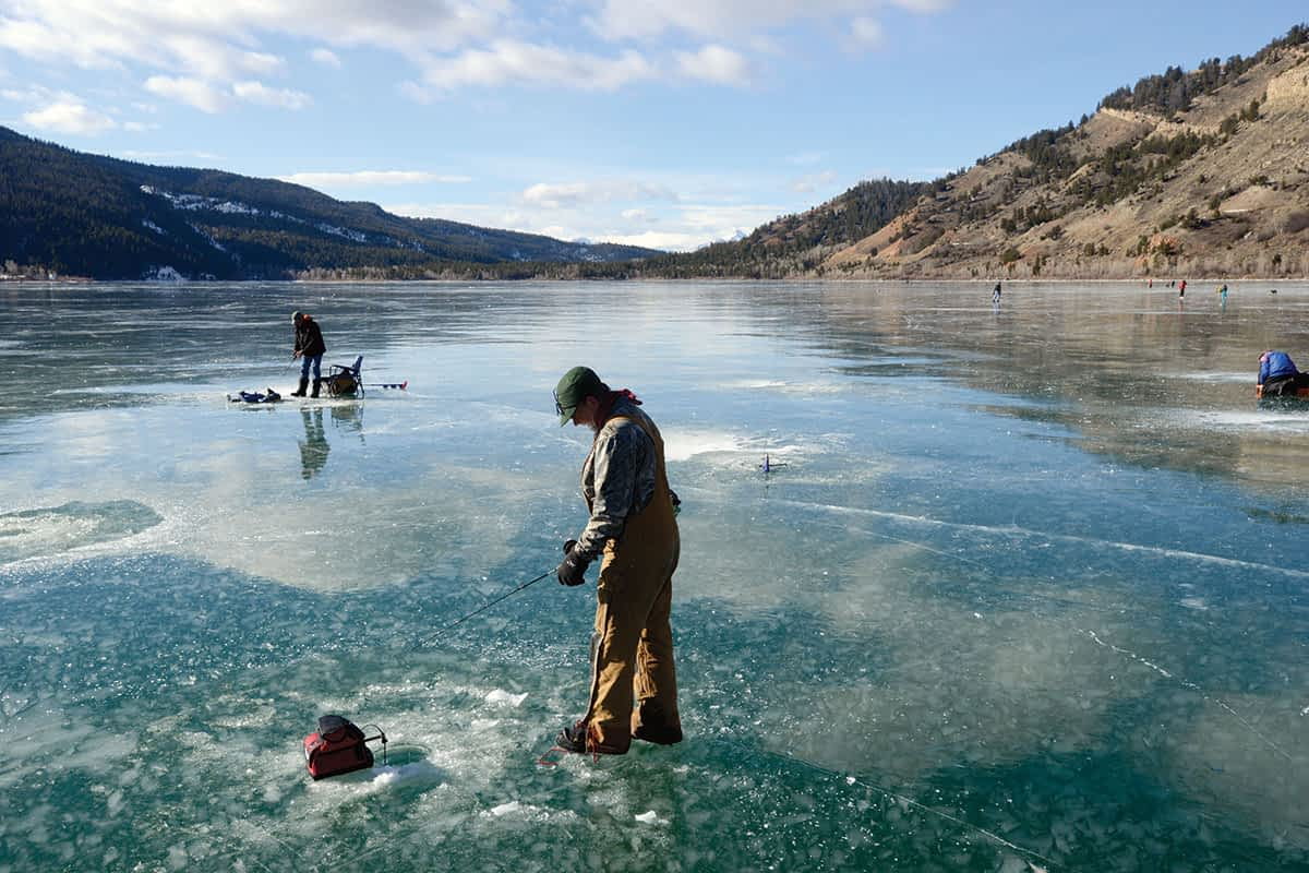 """Mike Braghini and Keith McCoy watch their electronic fish finders as they fish for trout on Slide Lake. """"It's a wonderful thing when man can walk on water,"""" McCoy says."""
