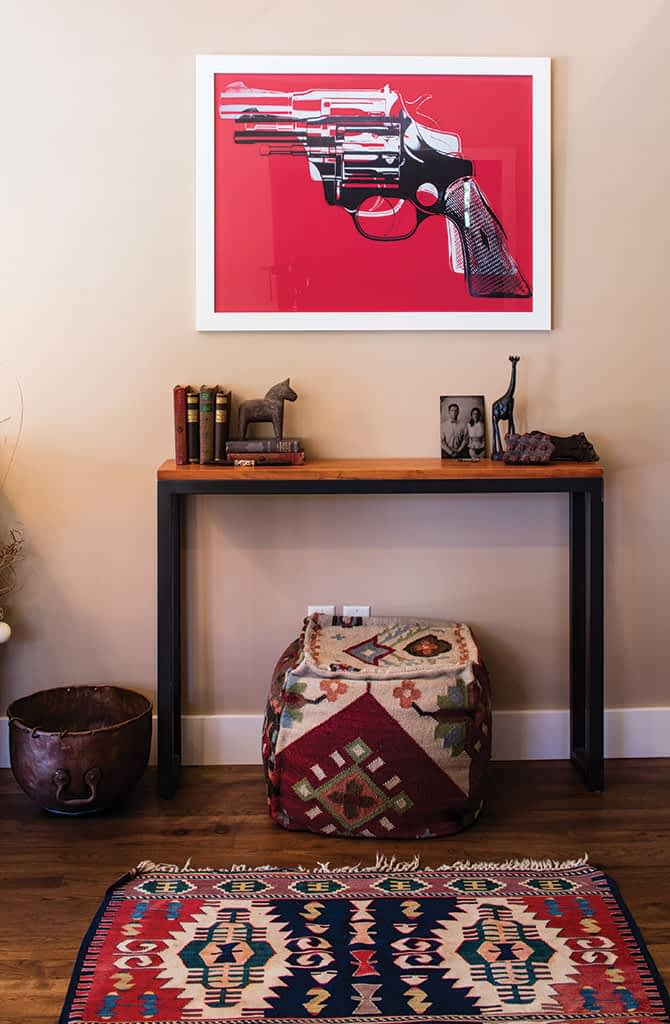A print of a gun painting from Andy Warhol's Death and Disaster series hangs at the entrance to the home.