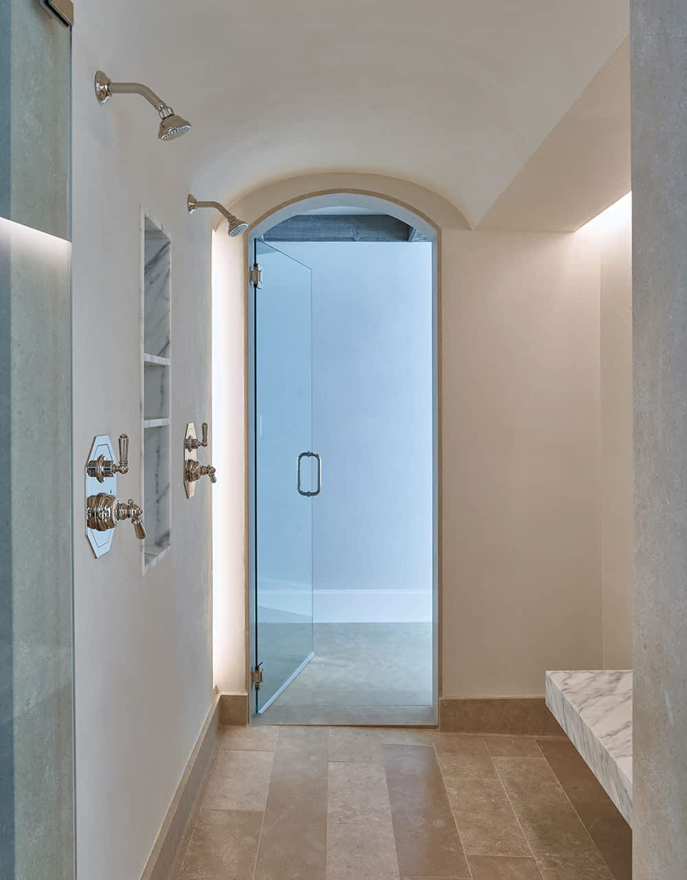 Showering is comfortable and glamorous with a cantilevered bench and honed and aged Calacatta marble. Walls are smooth plaster, and the floor is tumbled French limestone. All shower materials are from Concept Studio in Costa Mesa, California.