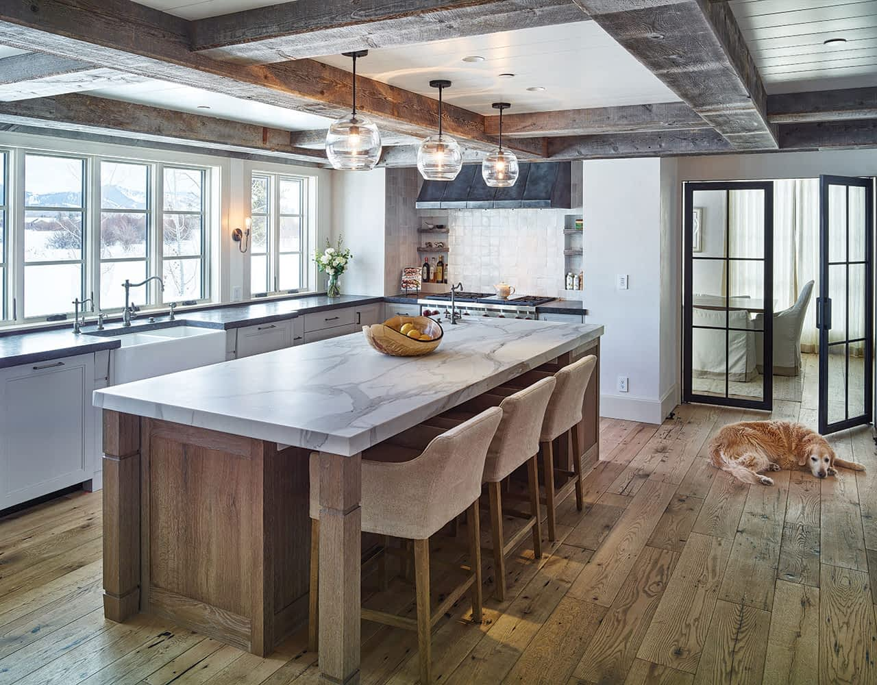 A marble counter provides a beautiful and functional space for cooking and entertaining. Steel doors by Jeff Brandner Designs in Bozeman, Montana, lead into the dining room. Willow Creek Woodworks of Idaho Falls built the Shaker-style cabinets.