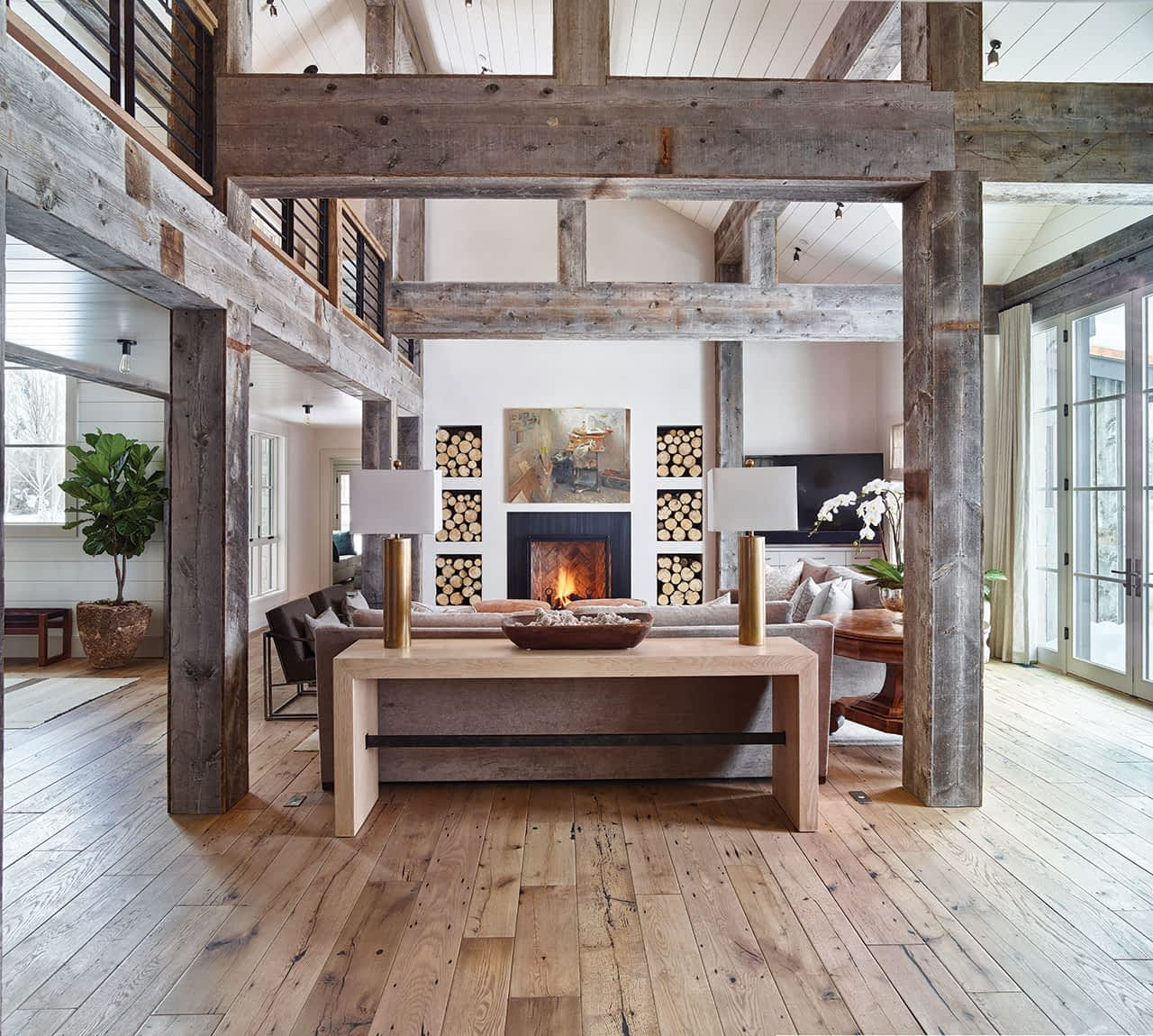 Reclaimed wood flooring in the living area lends an informal feel to the space. A Zoey Frank painting hangs above the fireplace.