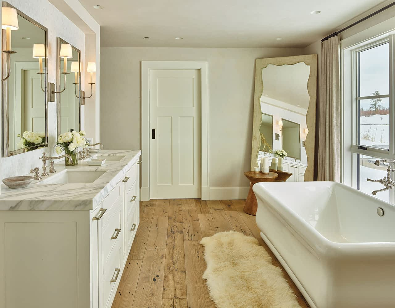 The vanity countertop is honed and aged Calacatta marble to match the shower bench. The faucets' finish is polished nickel. Hand-glazed Moroccan tiles decorate the vanity backsplash.