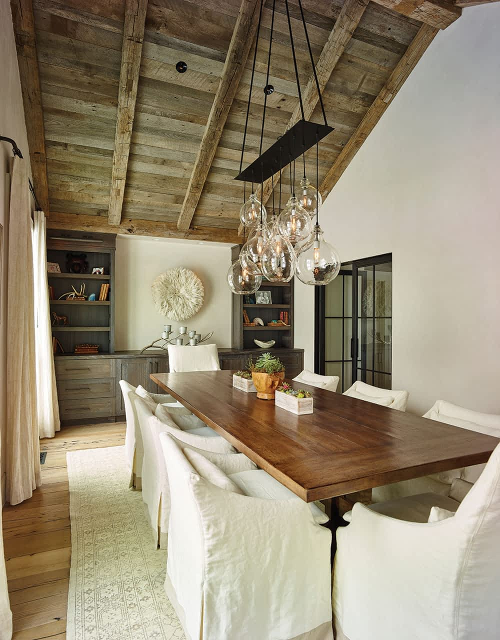 E2 Interior Design appointed the dining room with a white, feathered African JuJu headdress and a custom table built by California-based Laurie Flot. The chandelier—hand-blown glass with a steel canopy—is also custom, from Cisco Lighting.