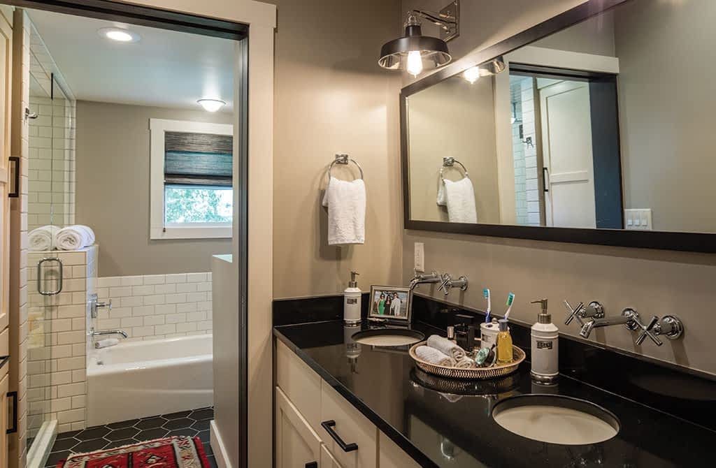The master bath has a walk-in shower and tub, both done with Daltile subway tiles. Full Circle Frameworks did the custom mirror.